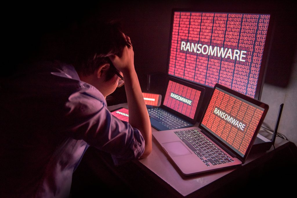 Frustrated man looking at ransomware warnings on multiple devices