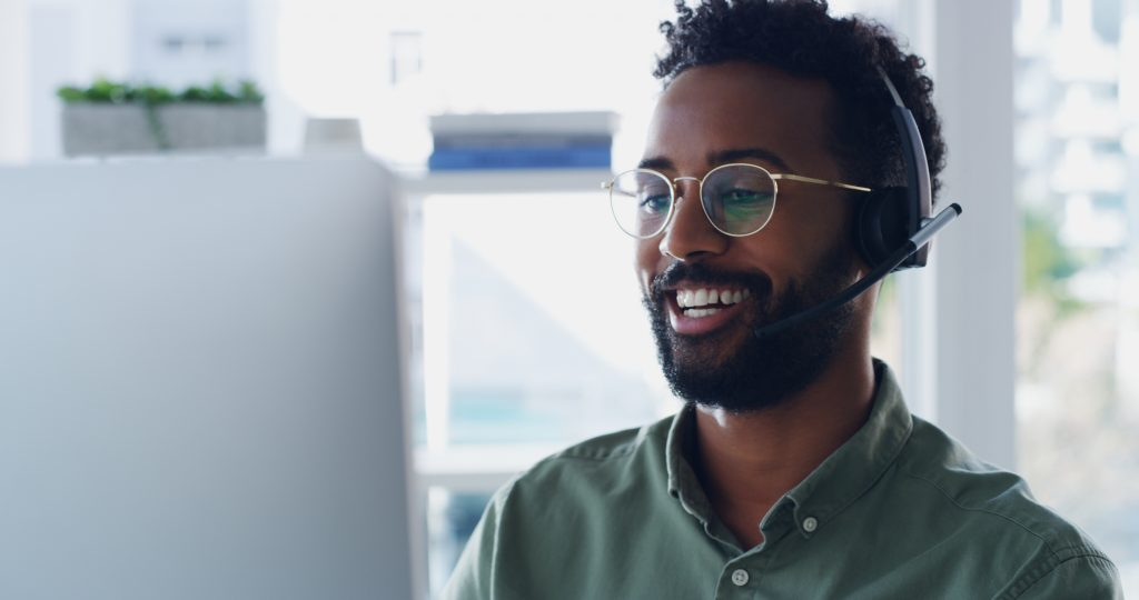 Smiling man with headset looking at computer screen