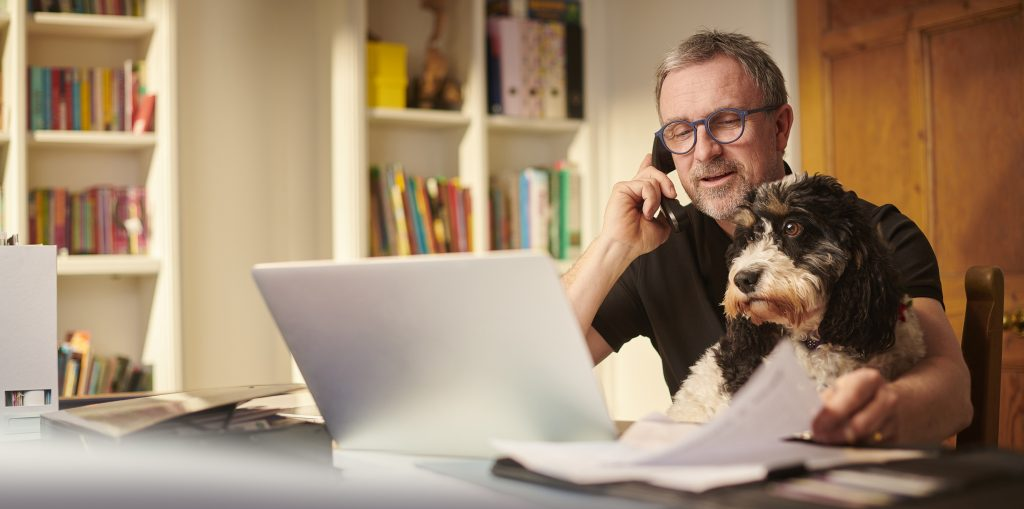 Man working from home with dog in his lap